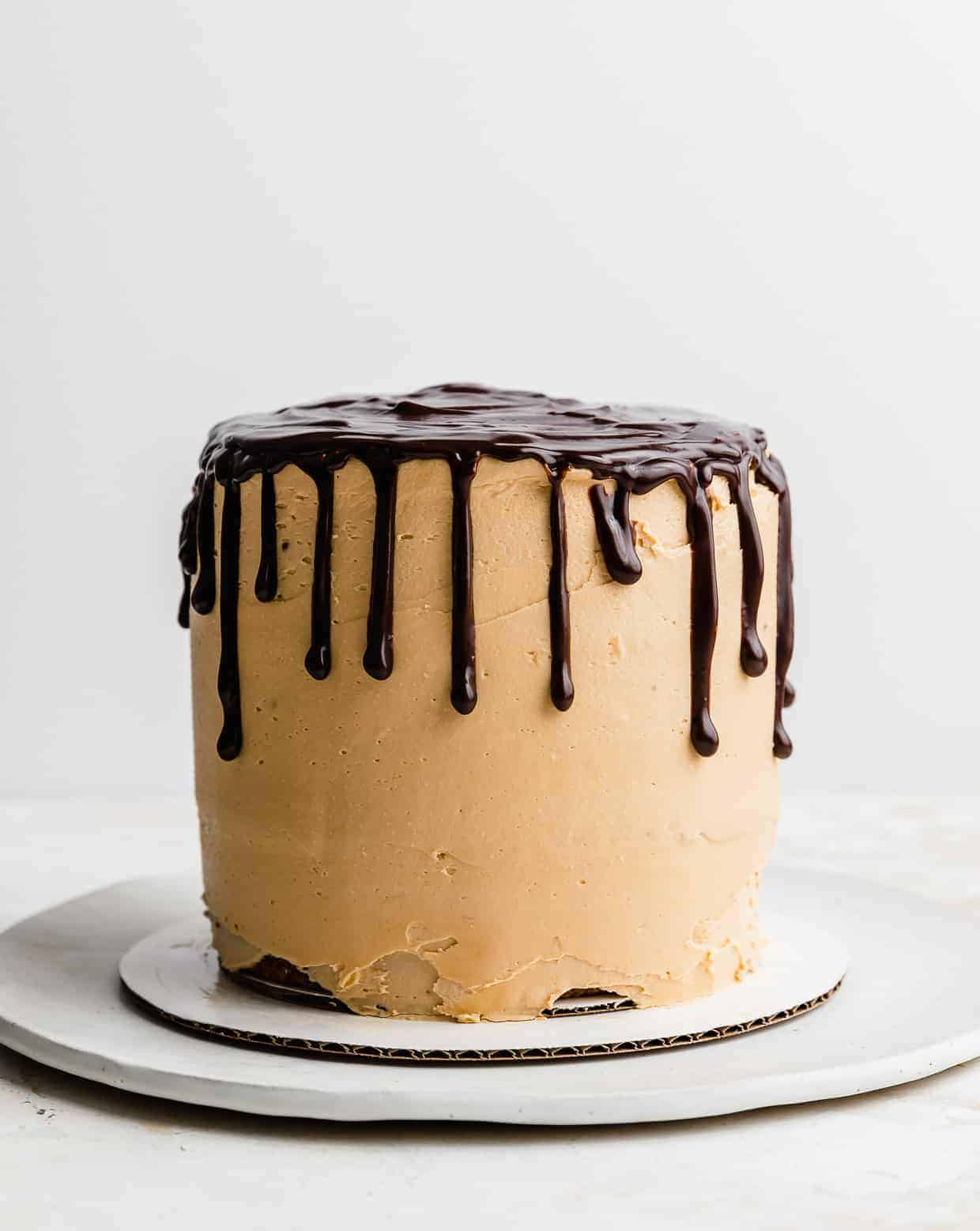 A butterscotch buttercream covered 7 Layer Bar Cake with a chocolate drip going down the sides.