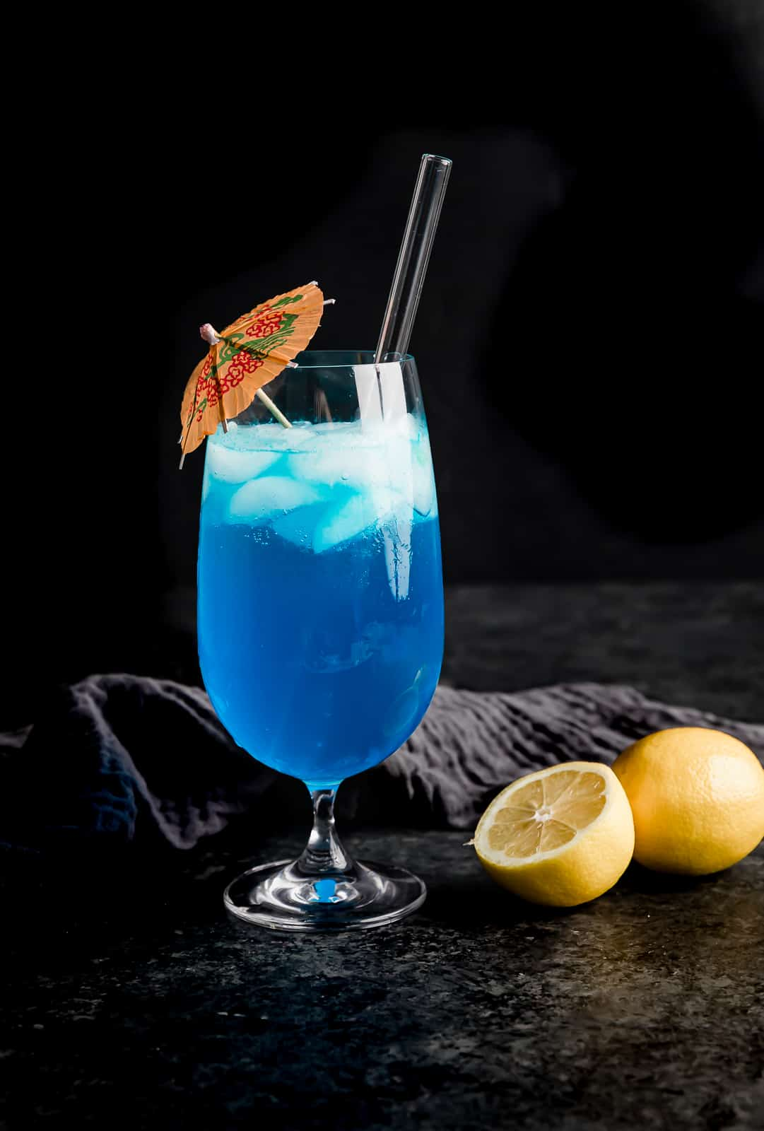 A glass cup full of a blue lagoon drink with a pink umbrella in the cup.