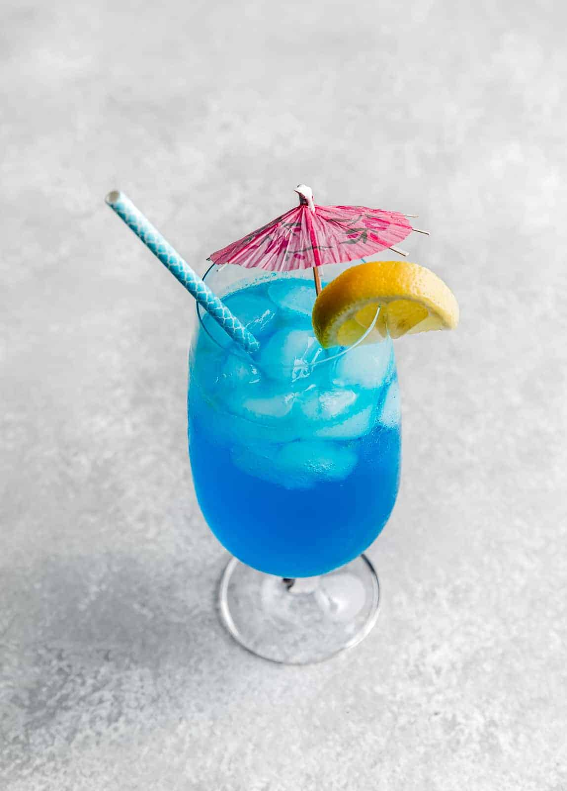 A blue lagoon mocktail drink on a gray background with a pink umbrella and lemon wedge on the edge of the cup.