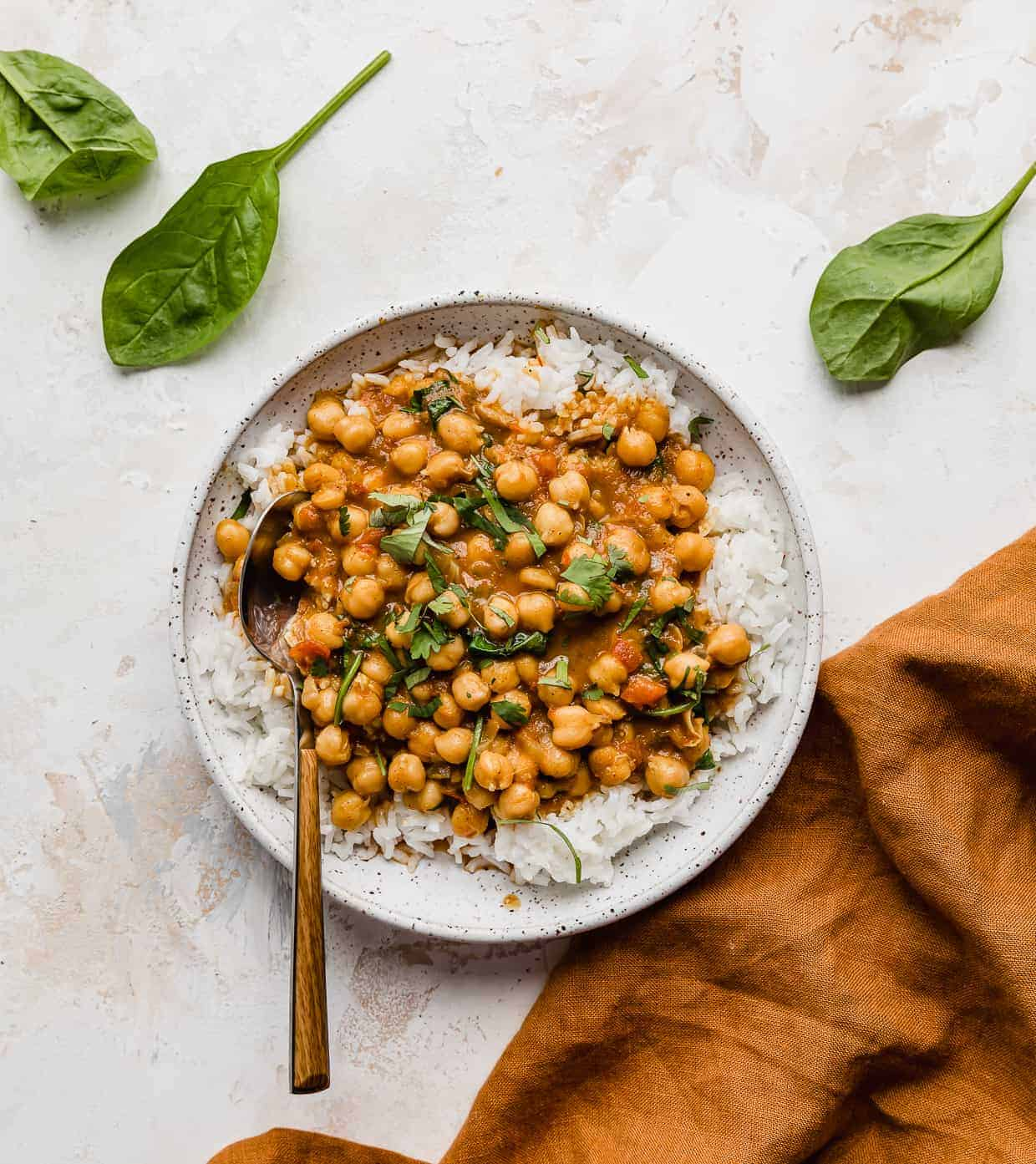 Chickpea and Spinach Curry on a white plate with spinach leaves on the side.