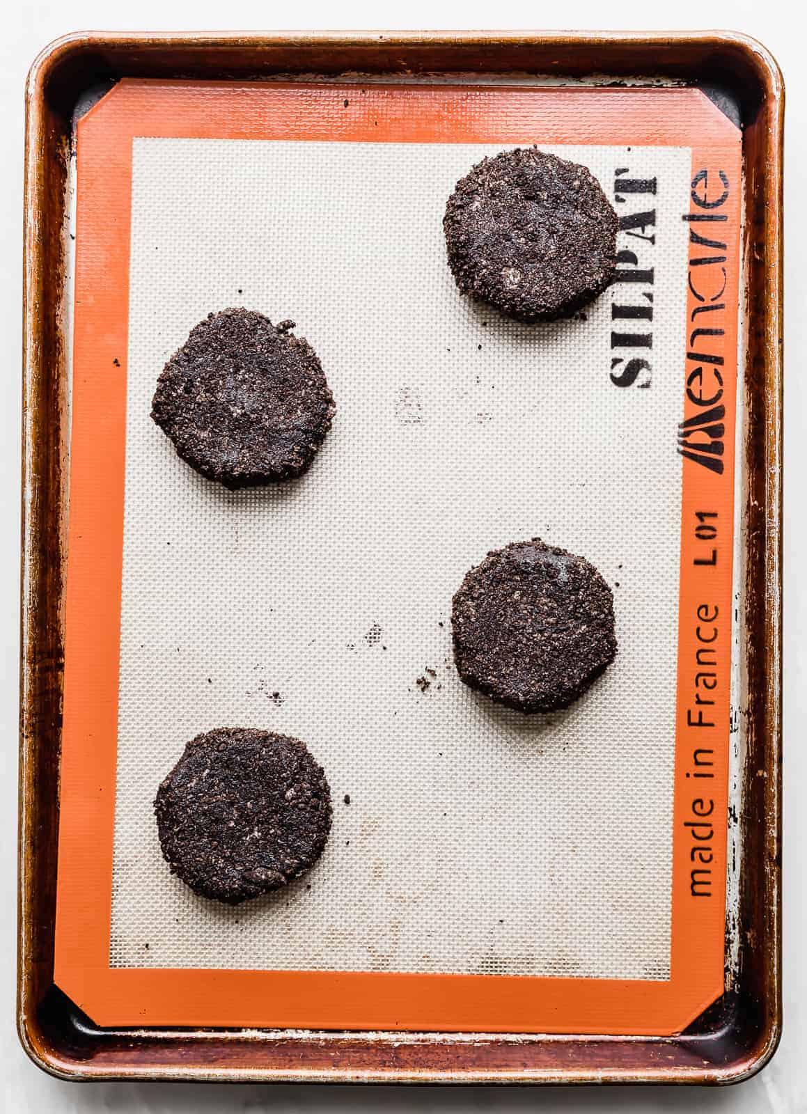 Black cookie dough batter balls on a baking sheet.