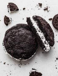 A copycat Crumbl Oreo cookie sandwich on a white background with Oreo crumbs surrounding the cookie.