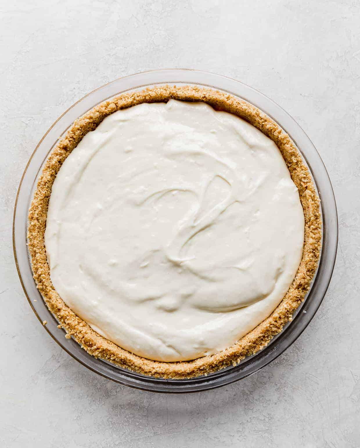 A Easy No-Bake Cheesecake in a graham cracker pie crust on a light gray background.