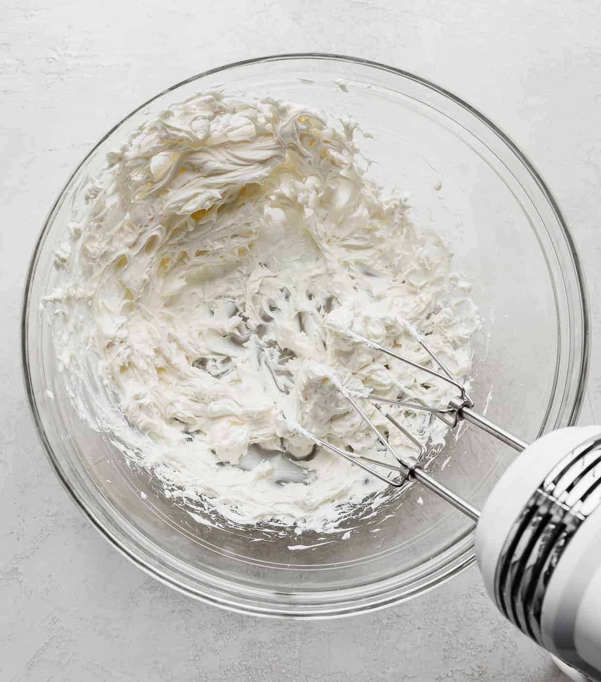 A glass bowl with cream cheese whipped in it.