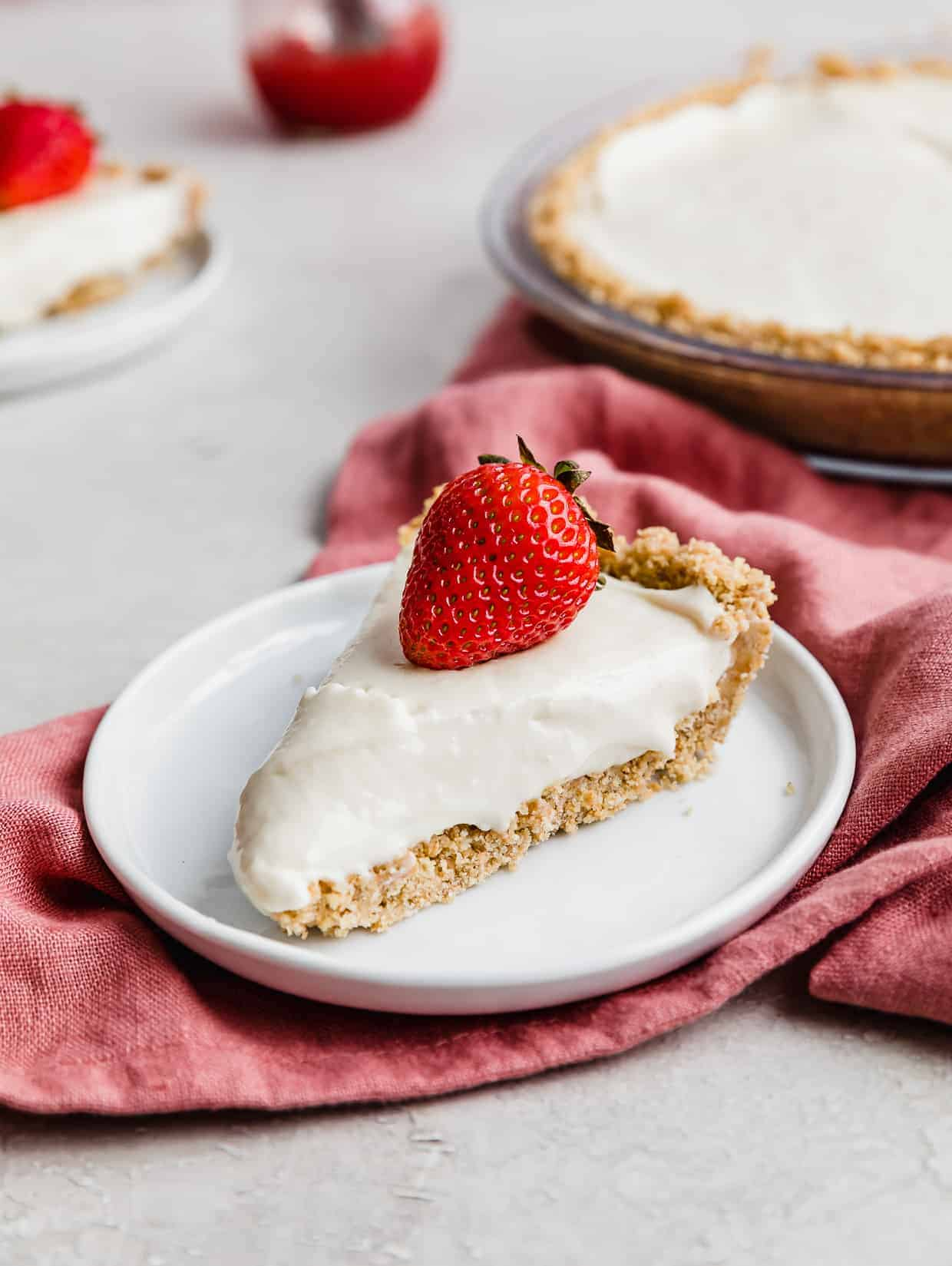 A slice of no-bake cheesecake on a white plate topped with a red strawberry.