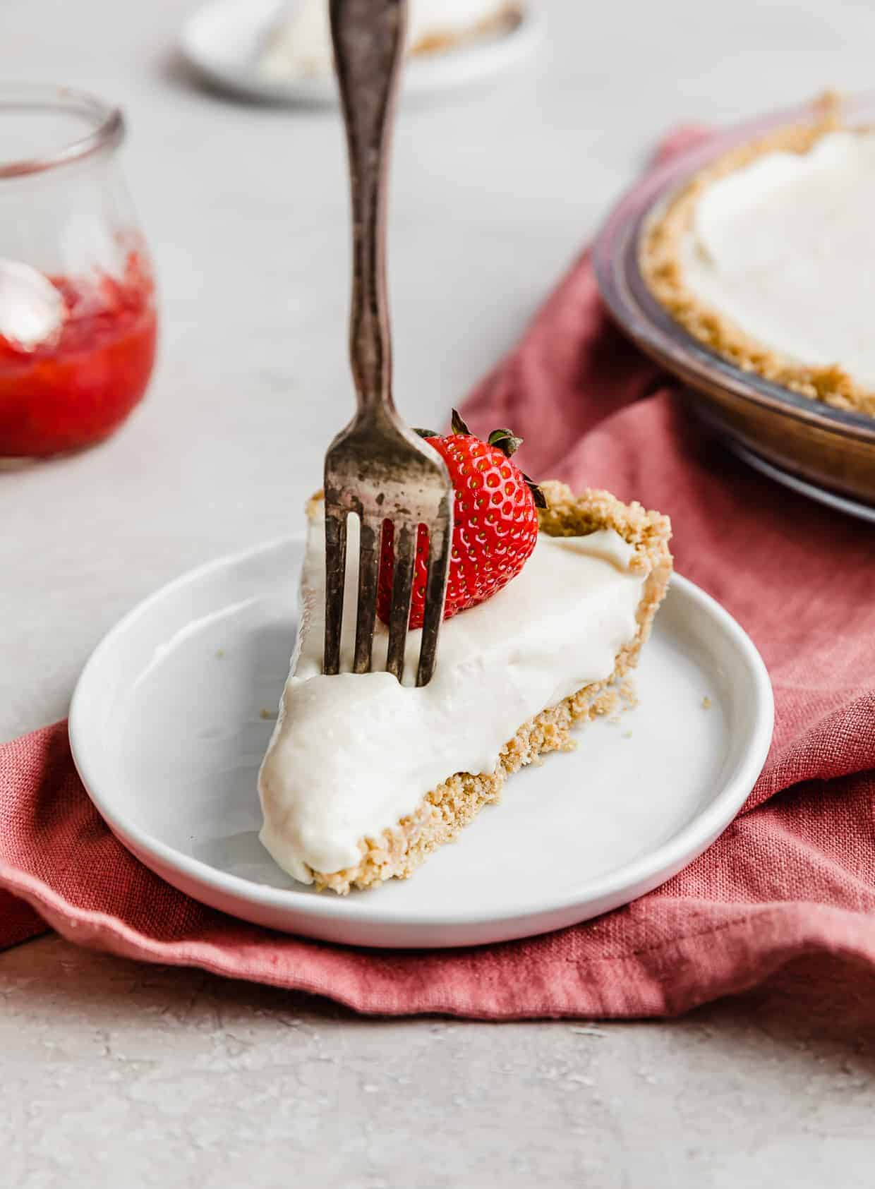A fork poking into a slice of no-bake cheesecake on a white plate.