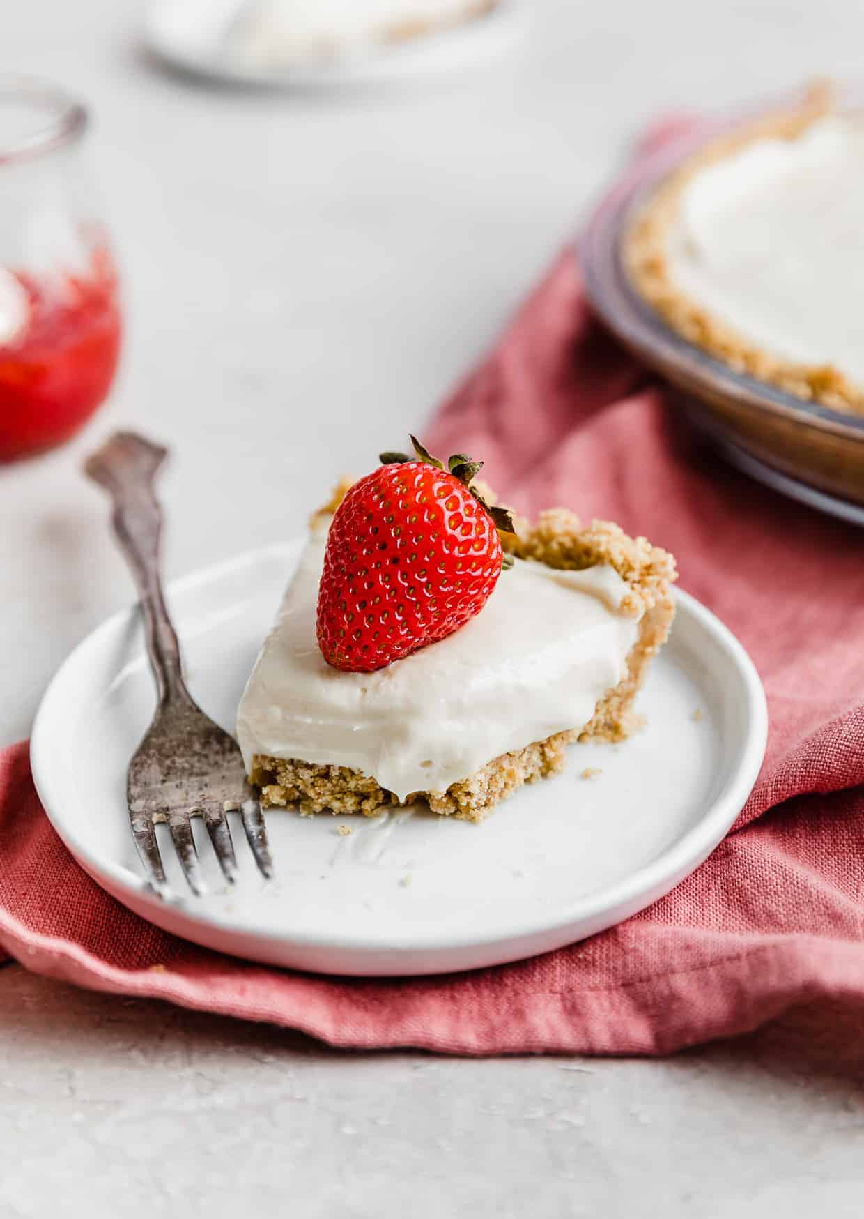 A strawberry on top of a slice of no-bake cheesecake on a white plate with a fork next to the cheesecake.