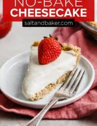 A slice of no bake cheesecake on a white plate topped with a fresh strawberry.