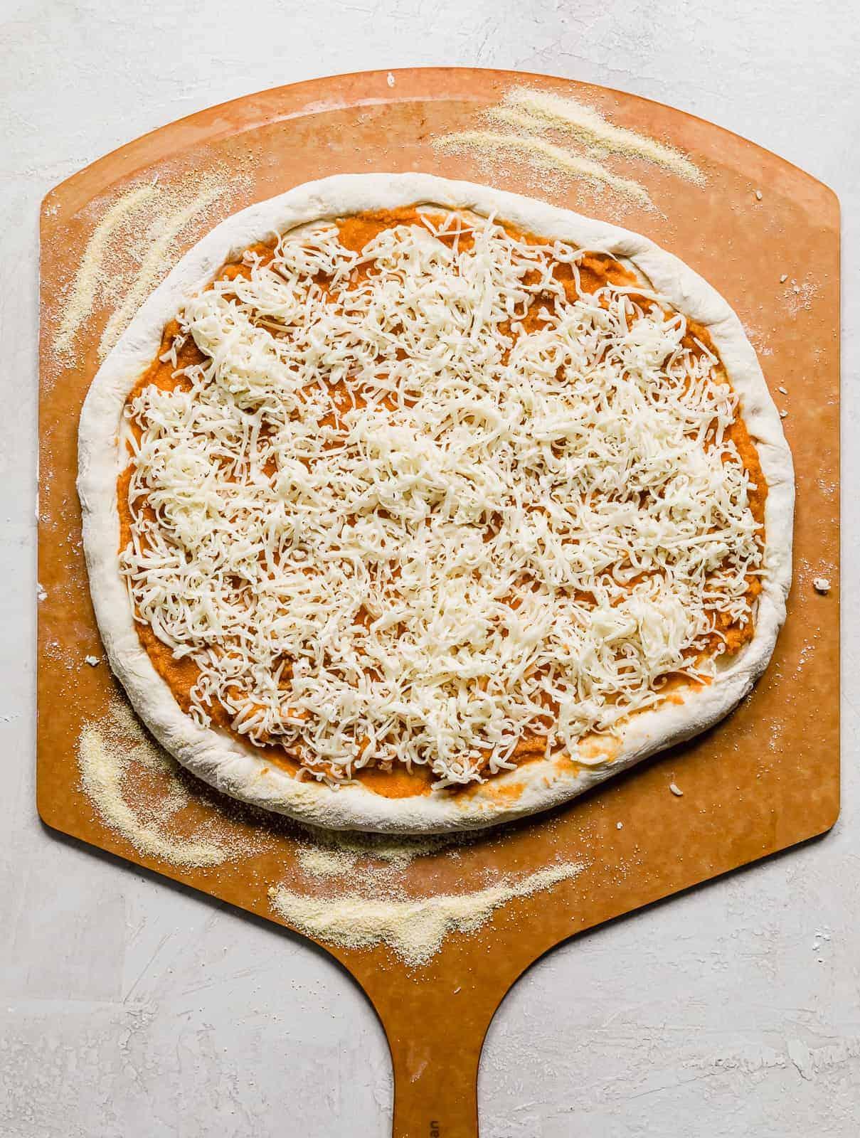 Shredded gouda cheese sprinkled over a pumpkin pizza on a pizza peel.