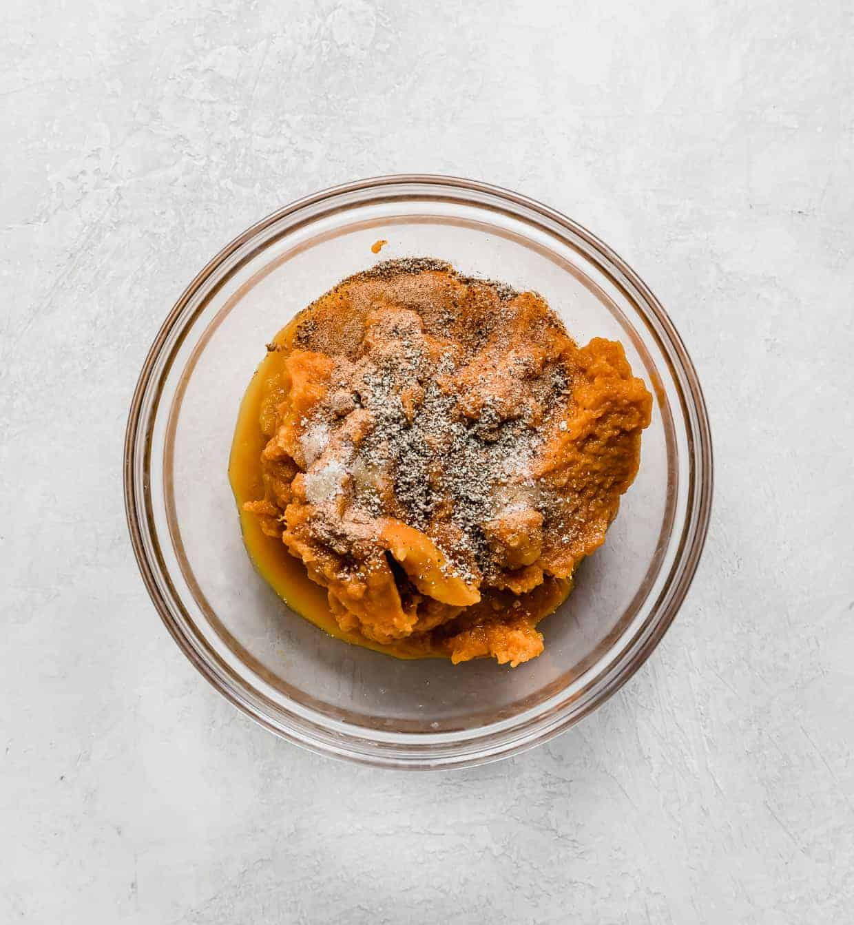 A glass bowl with pumpkin puree and spices.