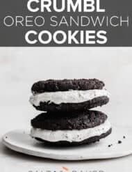 Two Oreo sandwich cookies stacked on top of each other, on a white plate.
