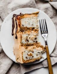 A slice of 7 Layer Bar Cake on a white plate.