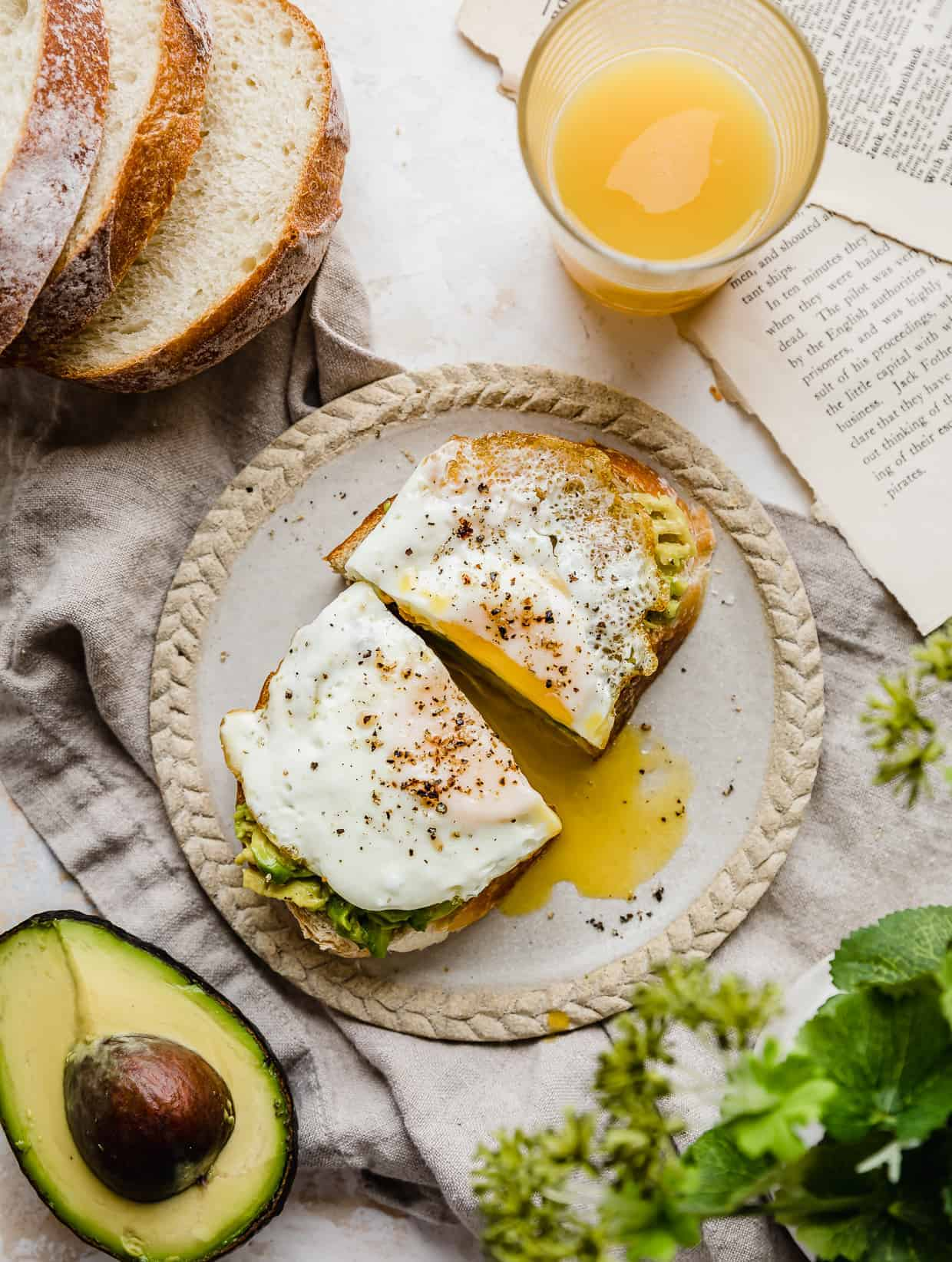 Avocado and Egg Toast cut in half on a plate.