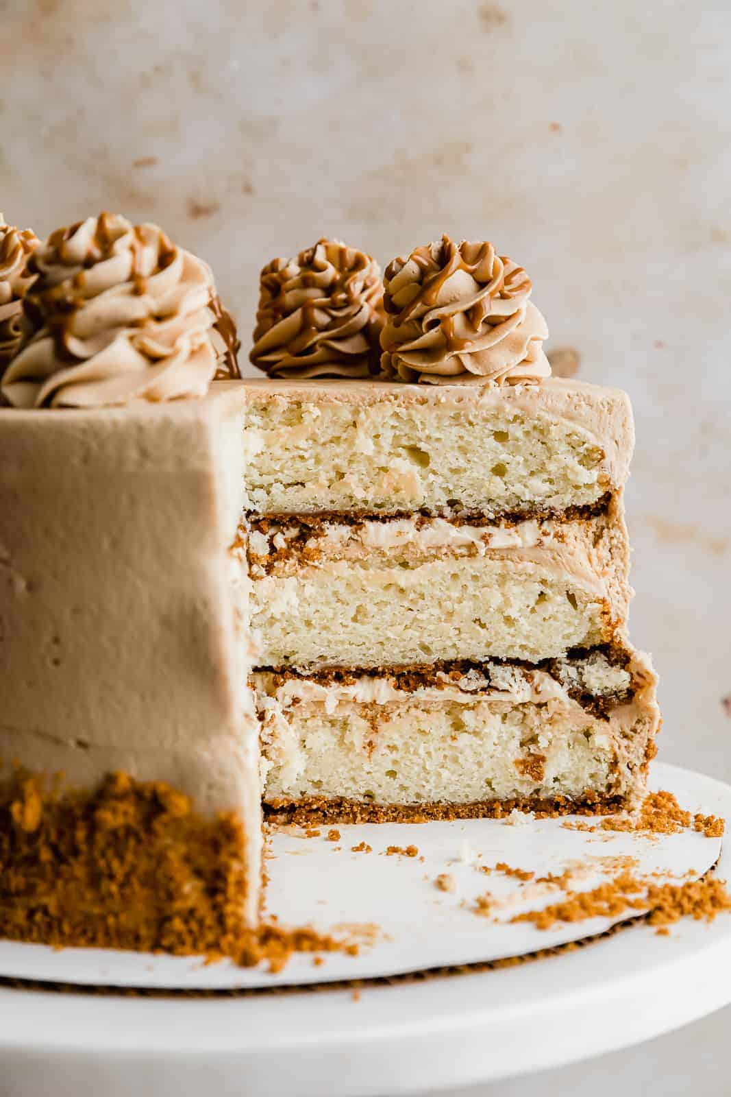 A Biscoff Cake with a slice taken out showcasing the three layers with a cookie butter crust.