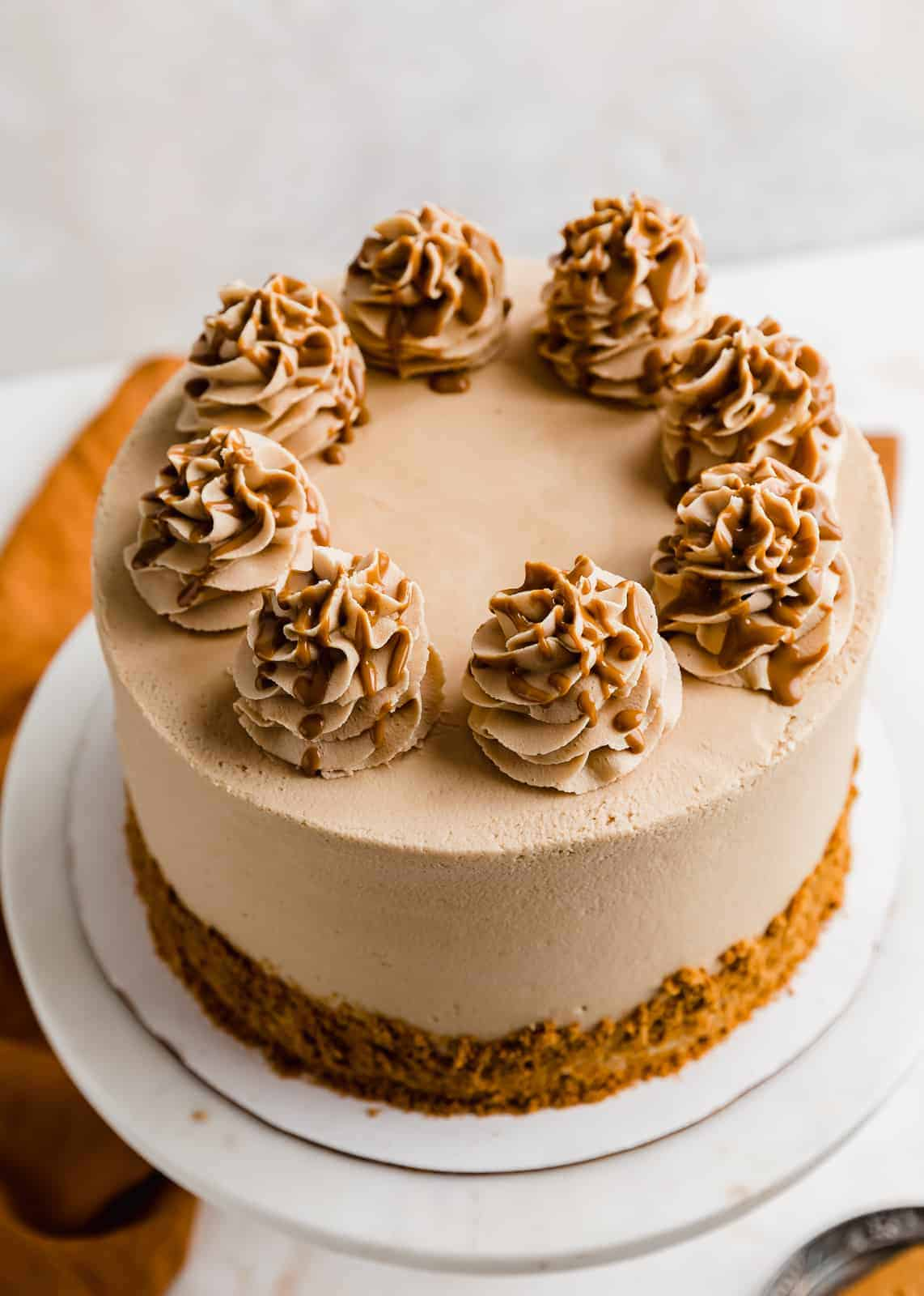 Overhead photo of a Biscoff cheesecake cake topped with swirls that are drizzled with Biscoff.