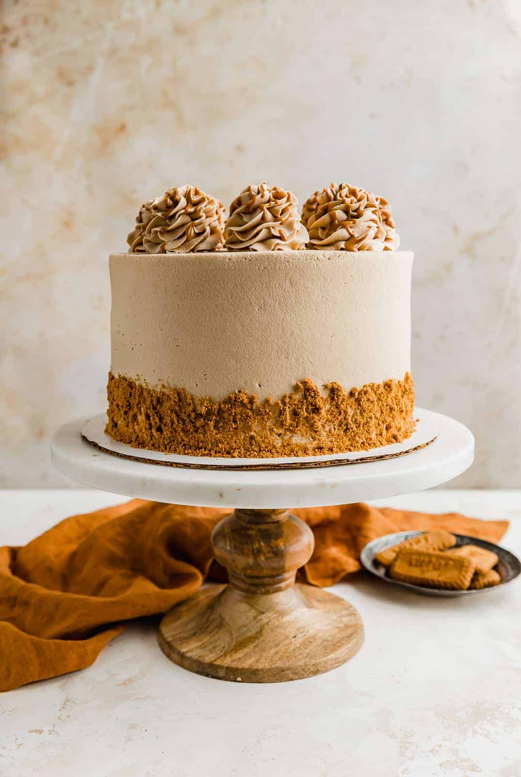 A Biscoff Cake on a cake stand with cookie crumbs on the sides.