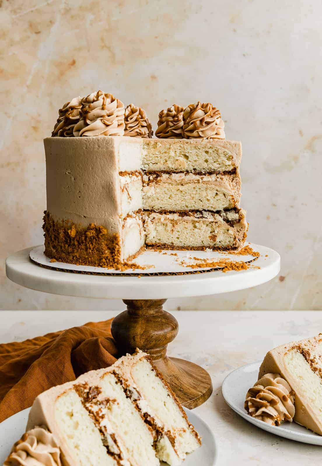 A Biscoff Cake against a cream background showing the 3 layers of cheesecake cake.