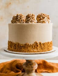 A Biscoff Caramel Cake on a marble cake stand against a cream colored background.