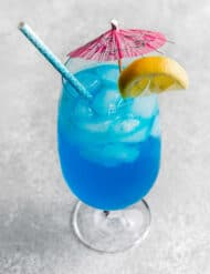 A Blue Lagoon Mocktail in a large glass cup with a pink umbrella and lemon slice on the rim.
