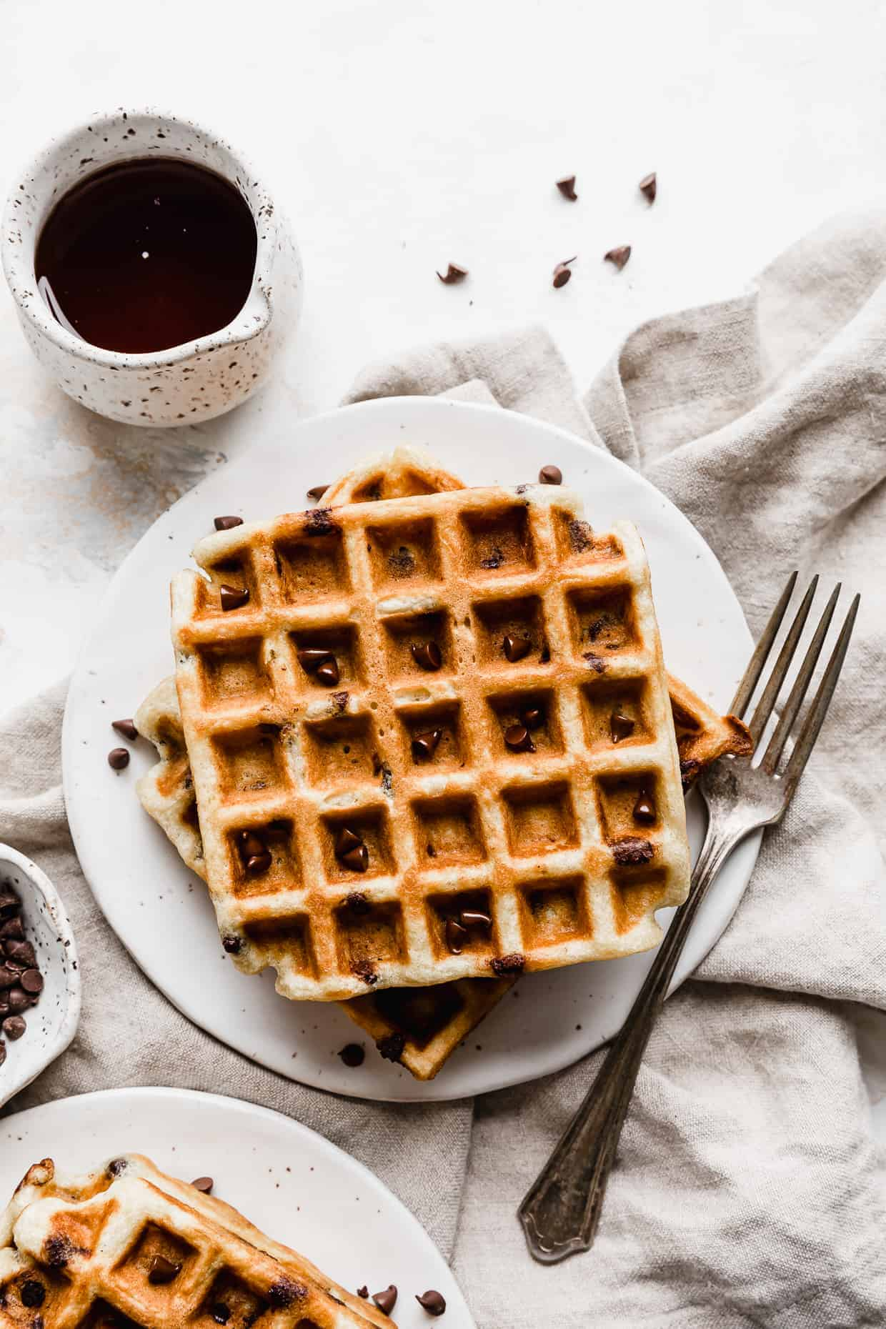 Chocolate Chip Waffles on a white plate with syrup in the left corner.