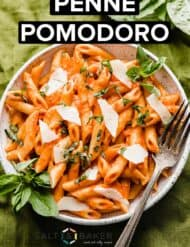 A plate full of homemade penne Pomodoro on a green background.