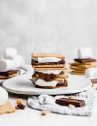 A stack of 3 s'mores on a white plate.