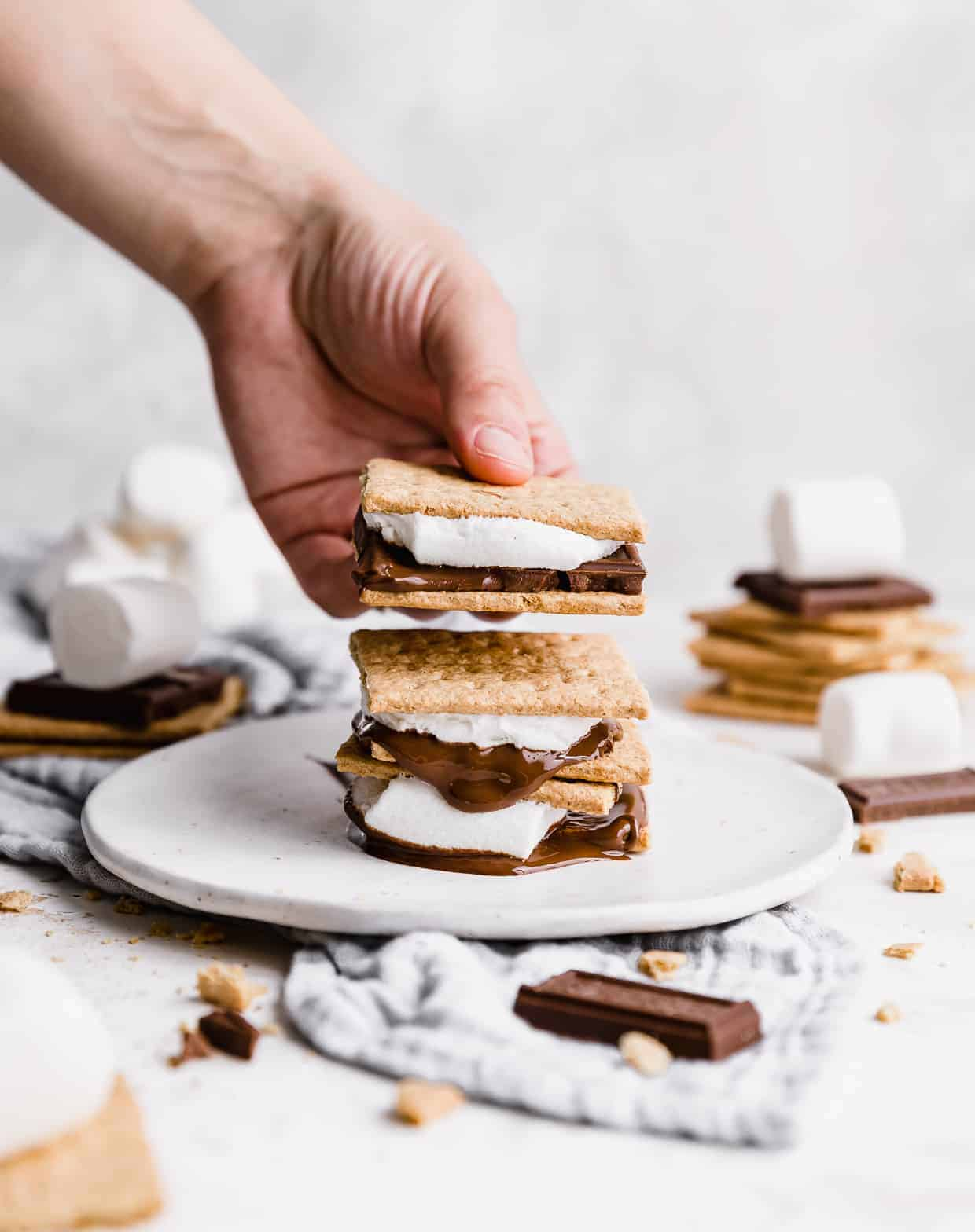 A hand holding a s'more against a white background.