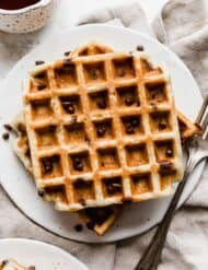 Chocolate Chip Waffles on a white plate with a fork to the right of the plate.