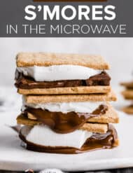 A stack of 3 s'mores on a white plate with chocolate dripping down the sides.