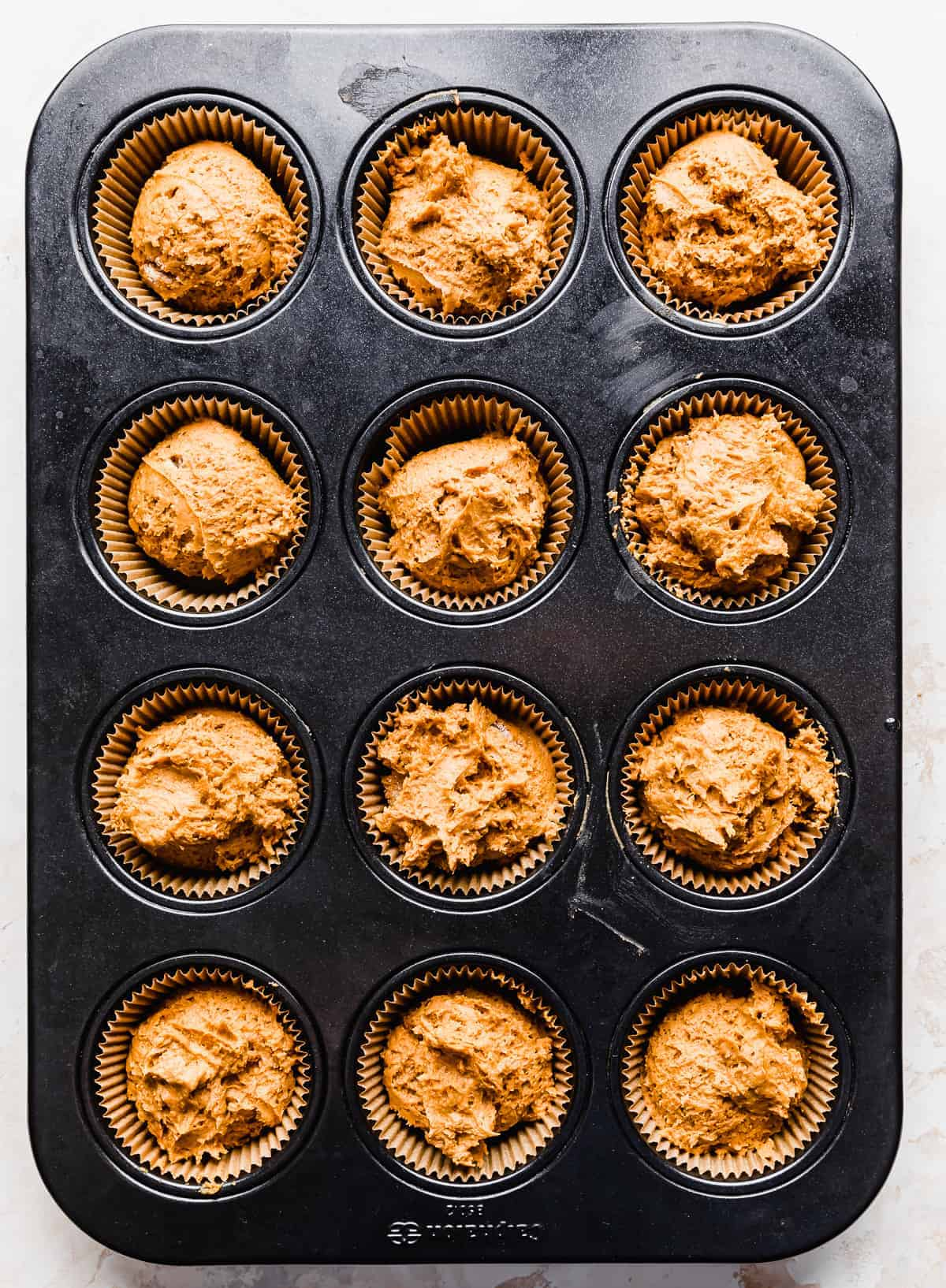 2 Ingredient Pumpkin Muffin batter in a lined muffin tin.