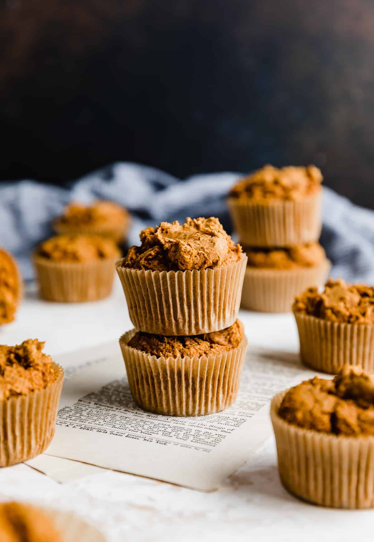 Two pumpkin muffins stack don top of each other against a brown background.