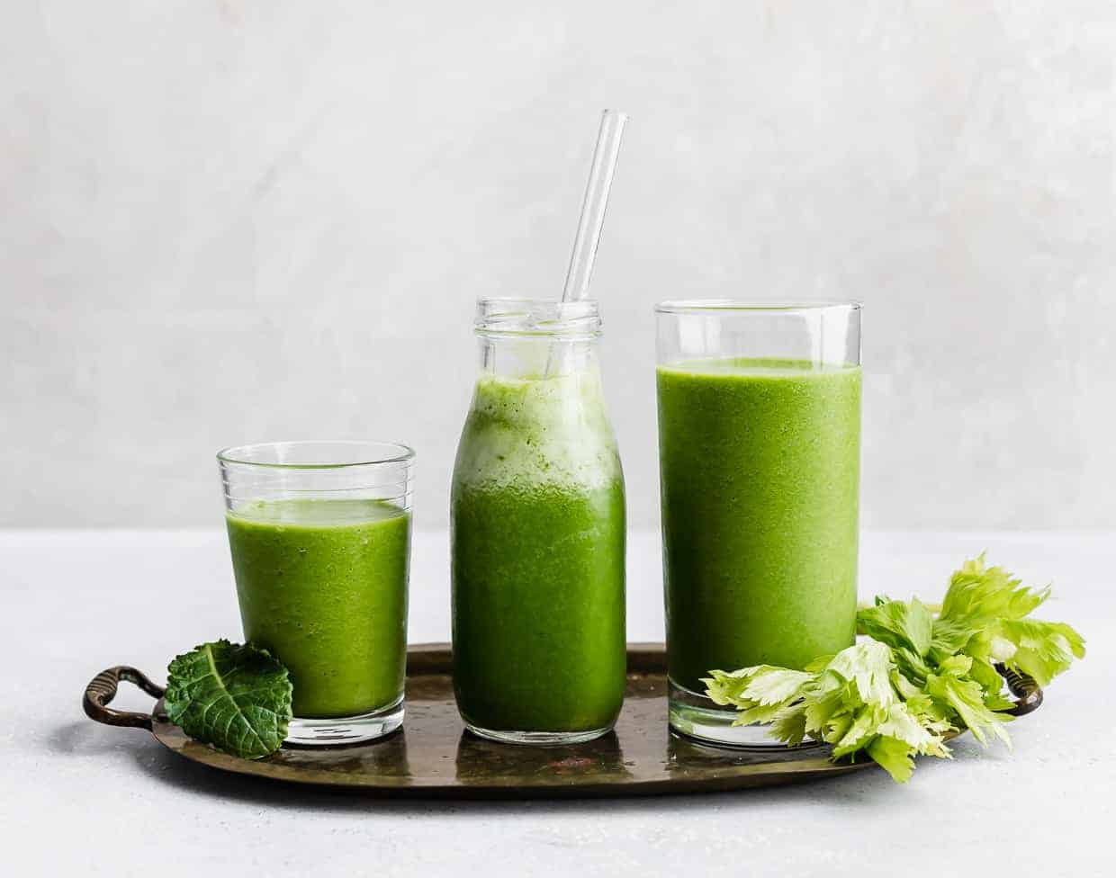 Three glasses full of green celery drink against a white background.