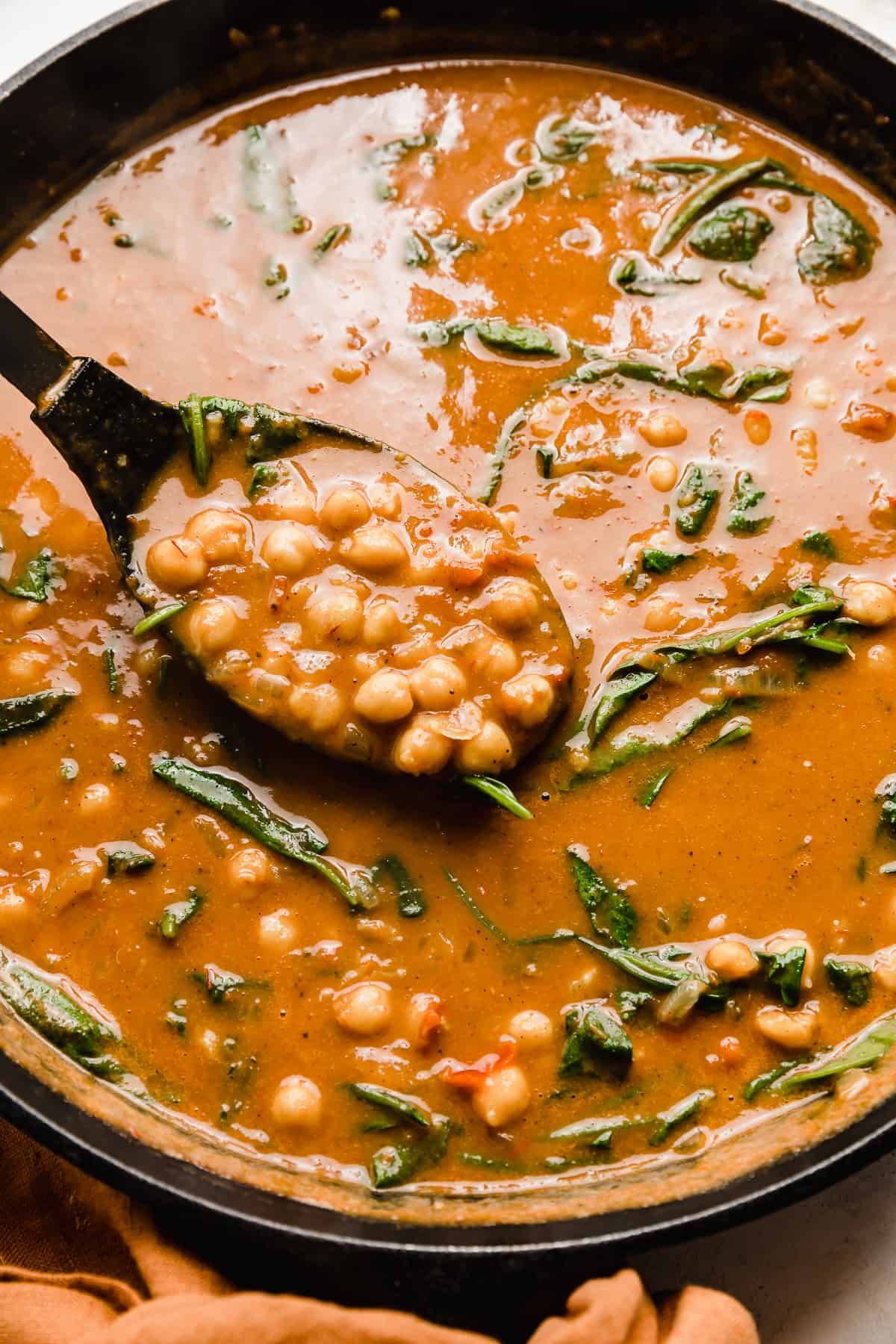A large spoon scooping up Chickpea and Spinach Curry from a black skillet.