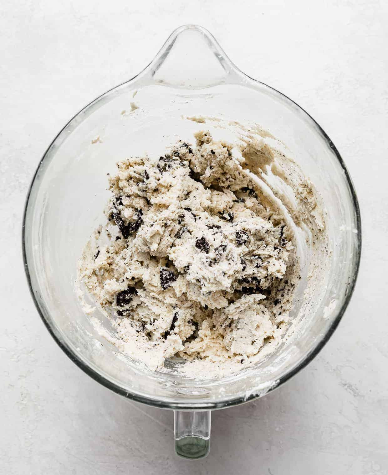 A glass bowl with a white cookie dough batter with Oreo chunks stirred into the mix.