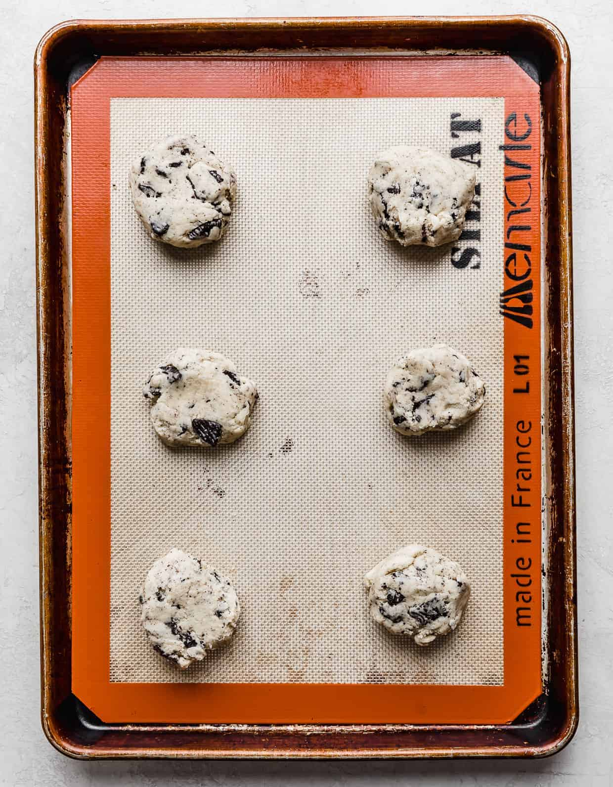 Six cookies and cream cookie dough balls on a baking sheet.