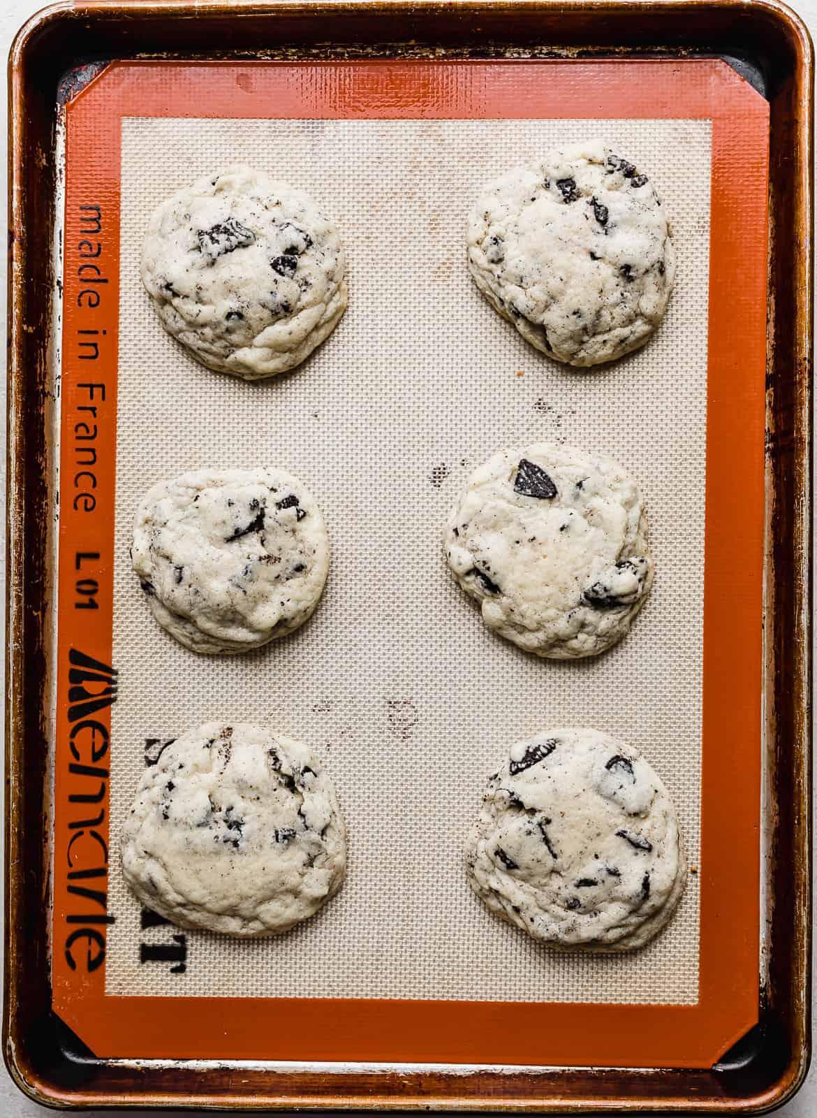 Six baked cookies and cream milkshake cookies on a baking sheet.