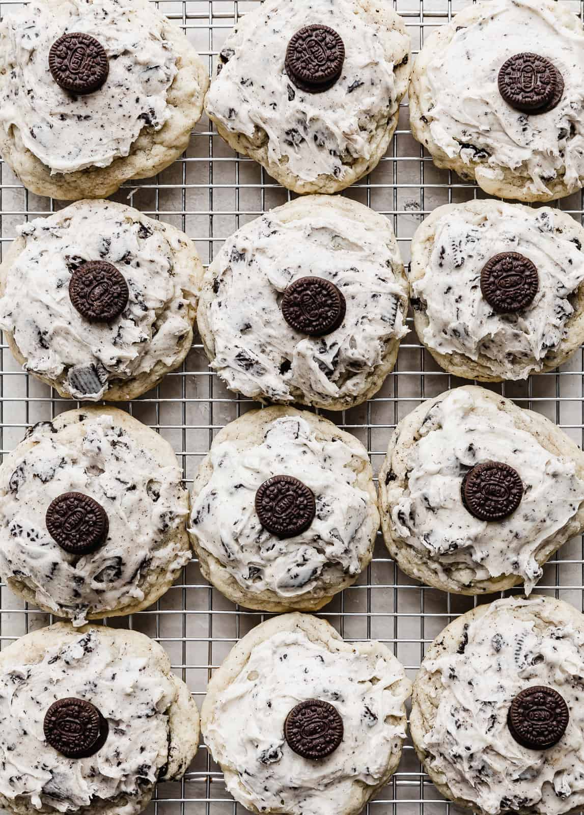 Crumbl Cookies and Cream Milkshake Cookies on a wire cooling rack, each with frosting and a mini Oreo on top.