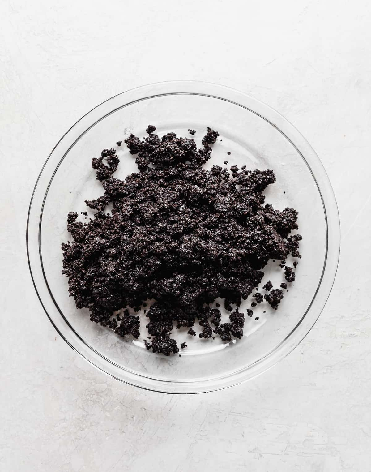 A glass pie dish with Oreo crumbs in it for making Oreo Pie Crust.