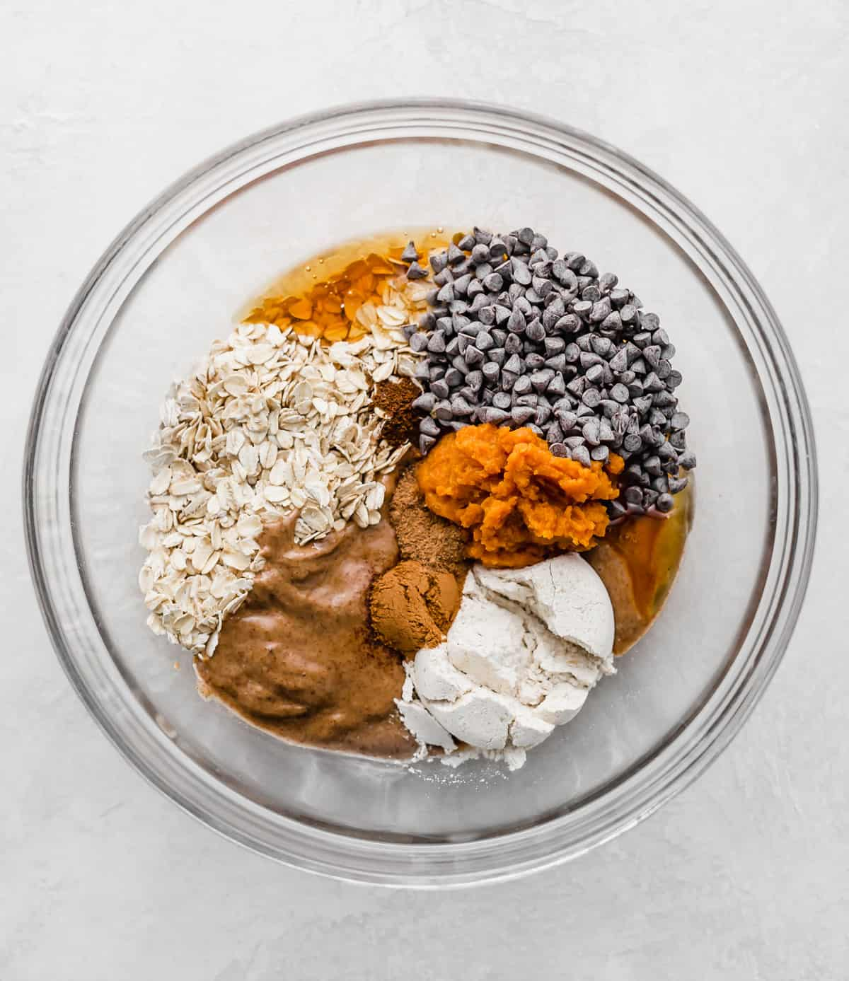 ingredients used to make pumpkin energy balls in a glass bowl.