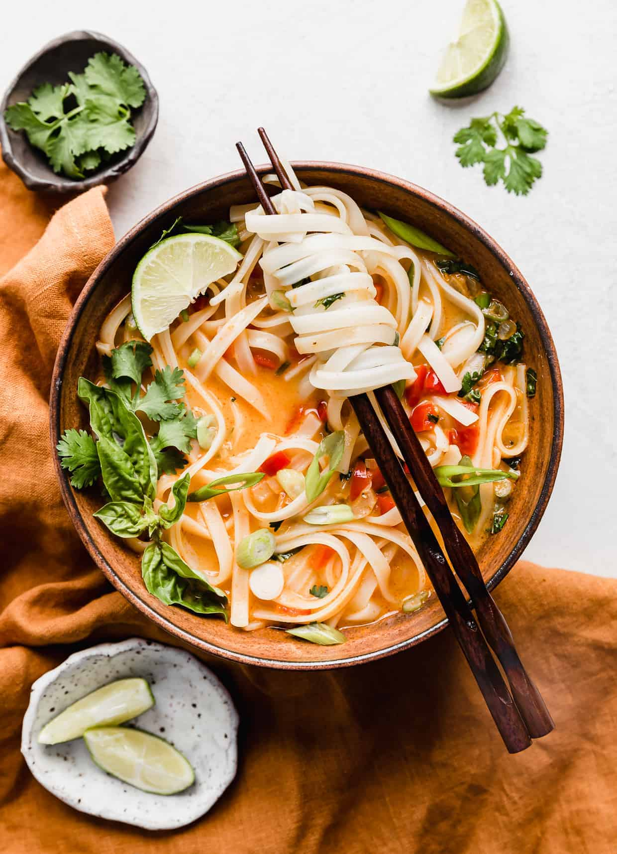 Thai Red Curry Noodle Soup in a brown bowl with chopsticks having rice noodles intertwined on the sticks.