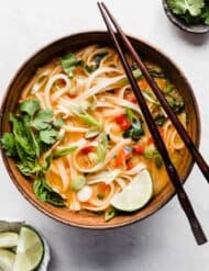 A bowl of Thai Red Curry Noodle Soup on a white background.