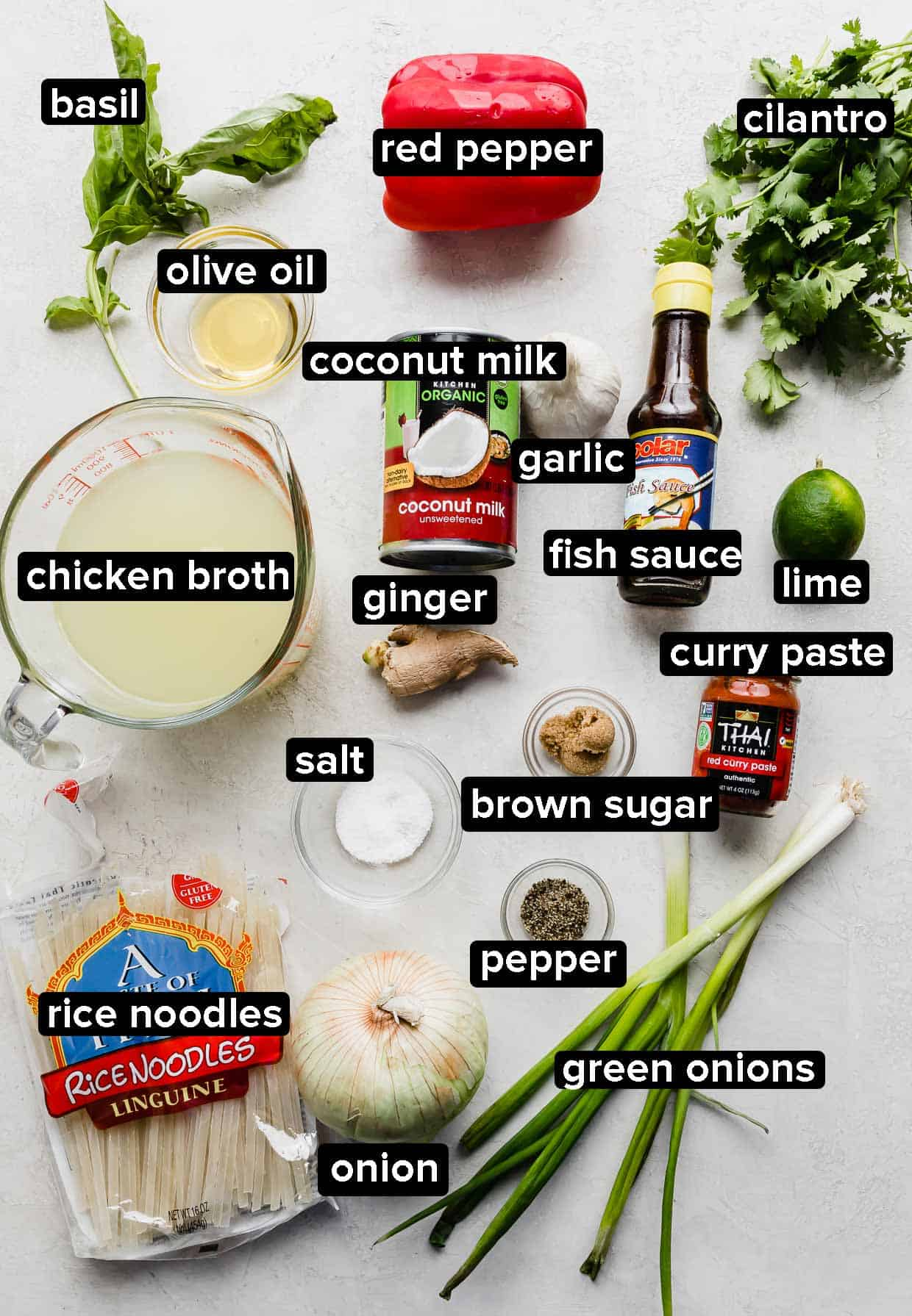 Ingredients used to make Thai Red Curry Noodle Soup on a white and gray background.