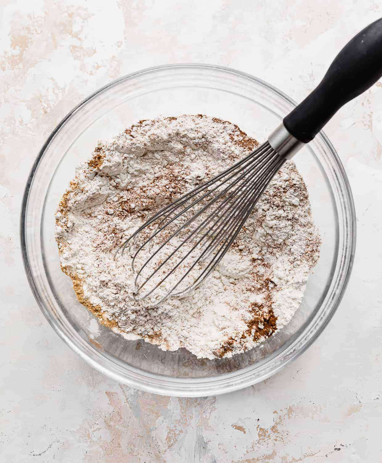 A whisk in a glass bowl full of dry ingredients used to make chocolate chip pumpkin pancakes.