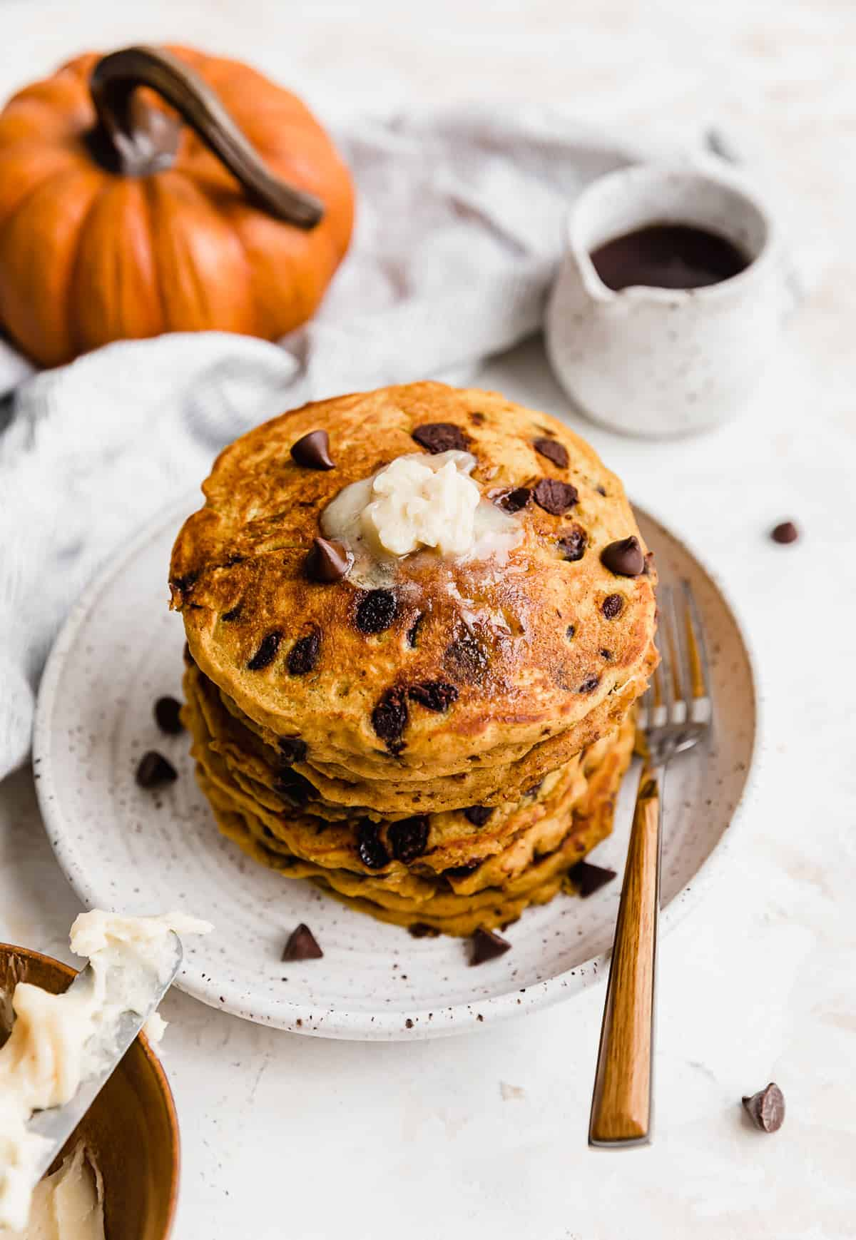 A stack of Pumpkin Chocolate Chip Pancakes on a white plate.