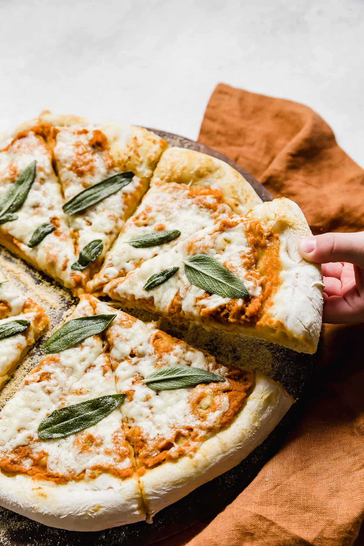 A hand pulling a slice of Pumpkin Pizza from the large pizza.