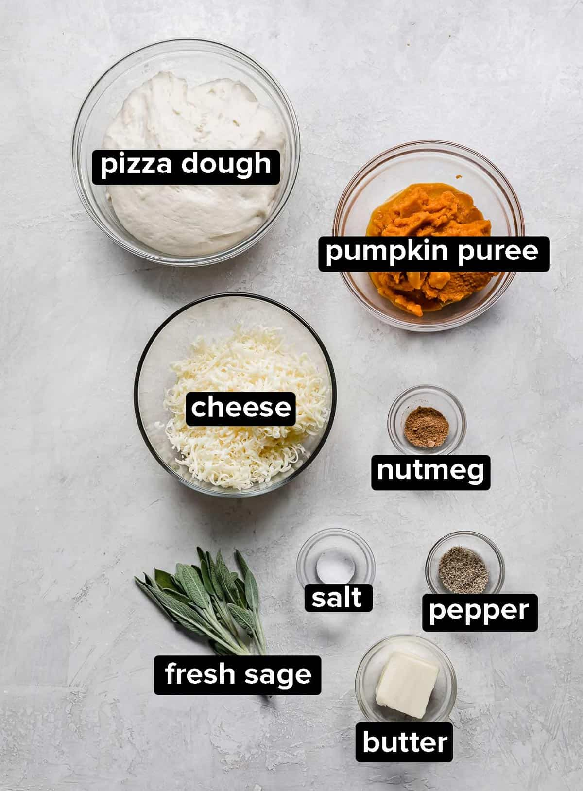 Pumpkin Pizza ingredients in glass bowls on a gray background.