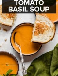 Three bowls of tomato basil soup, with half of a grilled cheese sandwich balanced on one bowl.
